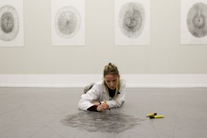 <p>Karoline Schreiber et un aspirateur automatique dessinent sur le sol / Photo: Marine Peixoto</p>